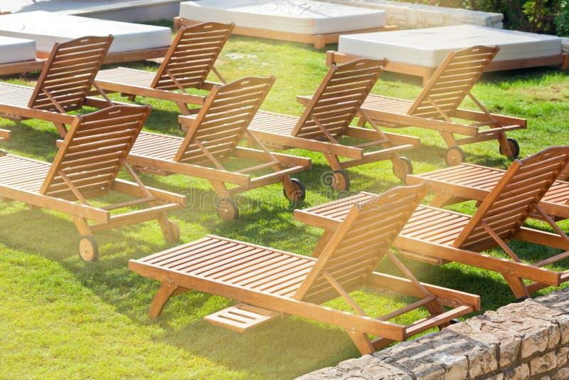 Стулья Poolside гостиницы на зеленом луге стоковое изображение rf