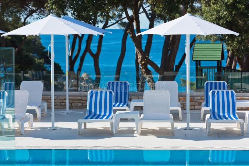Стулья Poolside гостиницы с видом на море стоковое фото