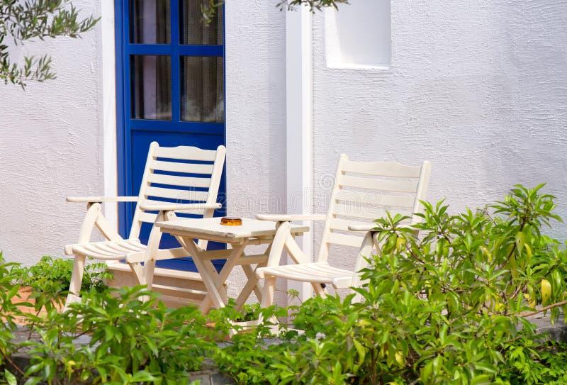 2 стуль и таблица около белого outdoors стены в Греции стоковое фото