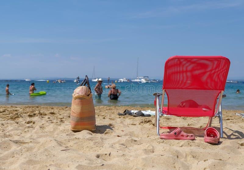 Стул и сумка аксессуаров пляжа красные на песке стоковое фото rf