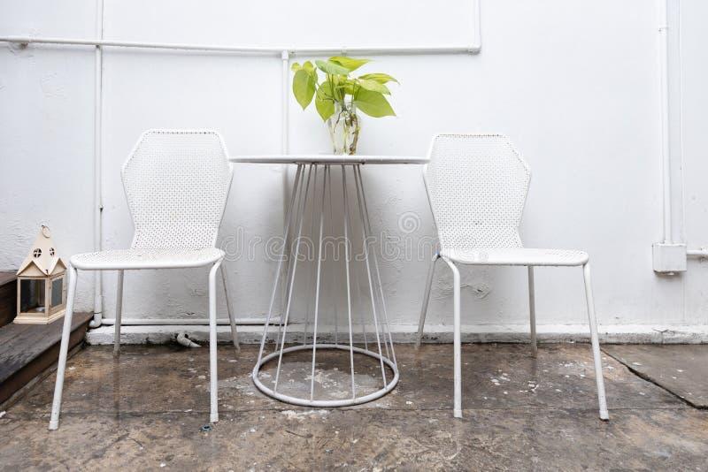 Стул и таблица металла белые на на открытом воздухе кафе в дождливом дне стоковые изображения rf