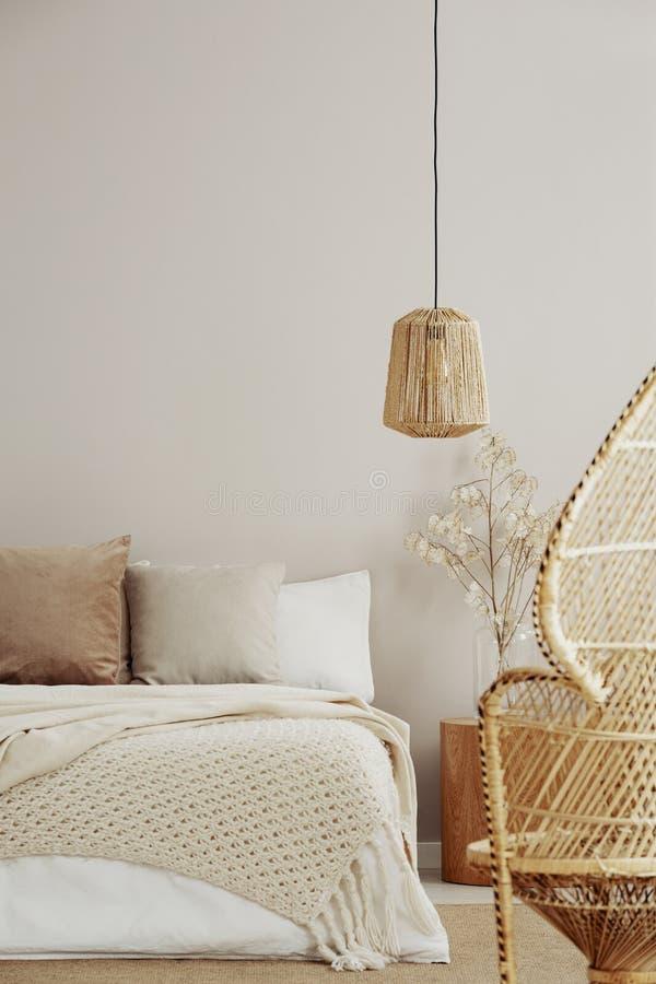 Стул павлина, плетеная люстра и уютная кровать, космос экземпляра на пустой стене стоковая фотография