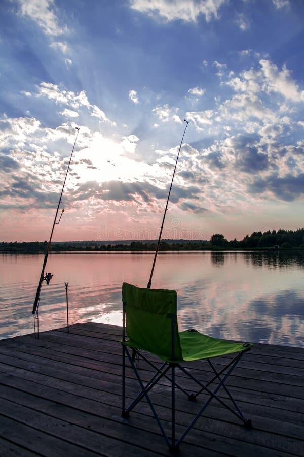 Стул складчатости и рыболовная удочка на озере стоковое изображение rf