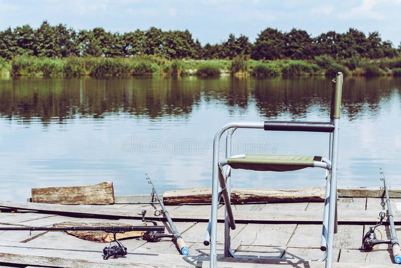 Стул складчатости, штанга для удить на деревянной пристани на береге реки Ретро тонизированное изображение оборудования рыбной ло стоковая фотография rf