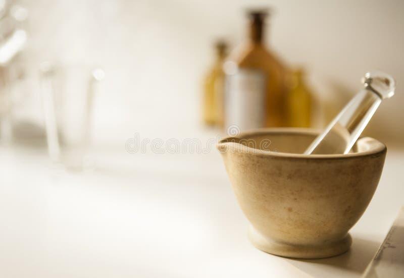 Ступка и пестик с пробиркой и бутылками снадобья стоковые изображения