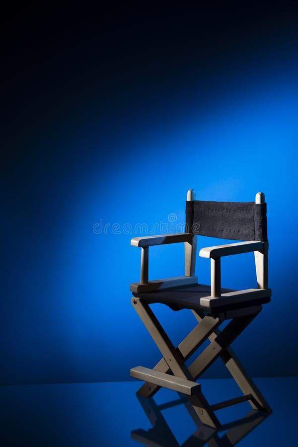 Стул директора на драматической освещенной предпосылке стоковые фото