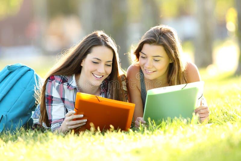 2 студента изучая примечания чтения outdoors стоковое изображение