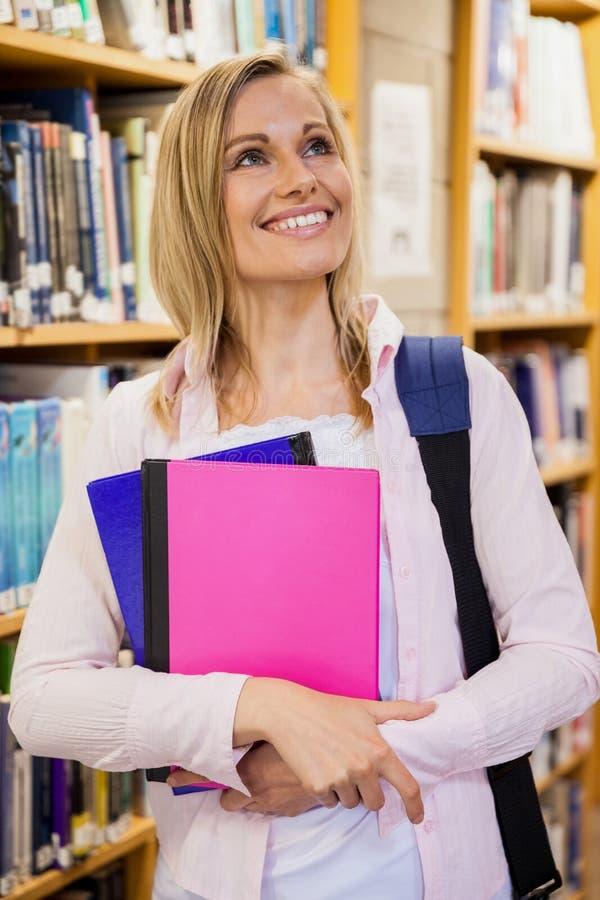 Студентка держа учебники в библиотеке стоковая фотография rf