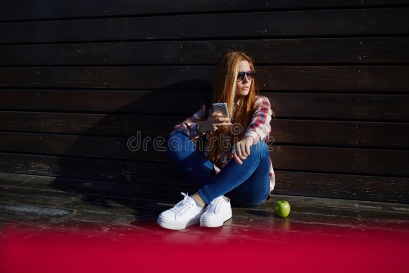 Студентка используя телефон клетки пока отдыхающ на кампусе после лекций стоковые фотографии rf