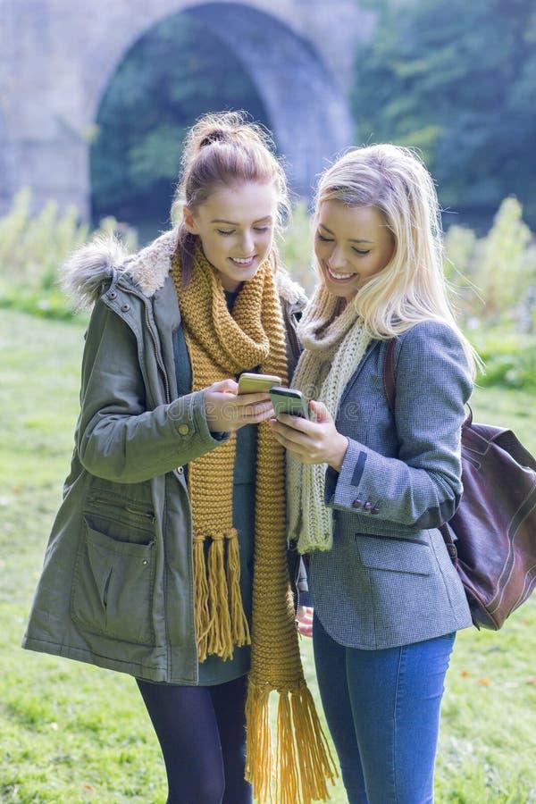 2 студентки используя их мобильные телефоны стоковое изображение