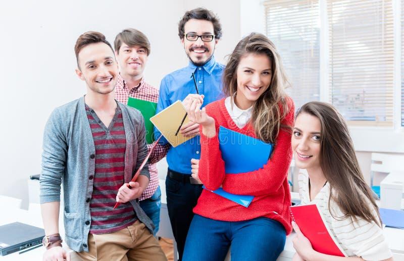 Студенты в коллеже или университете уча совместно стоковая фотография