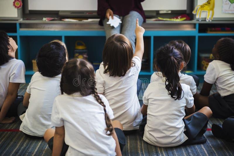 Студенты детского сада сидя на поле стоковое фото rf