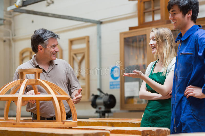 Студенты и учитель говоря и смеясь над в классе работы по дереву стоковые фото