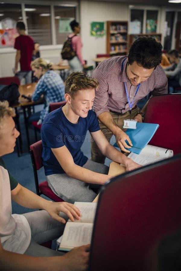 Студенты и учитель работая на компьютерах стоковая фотография rf