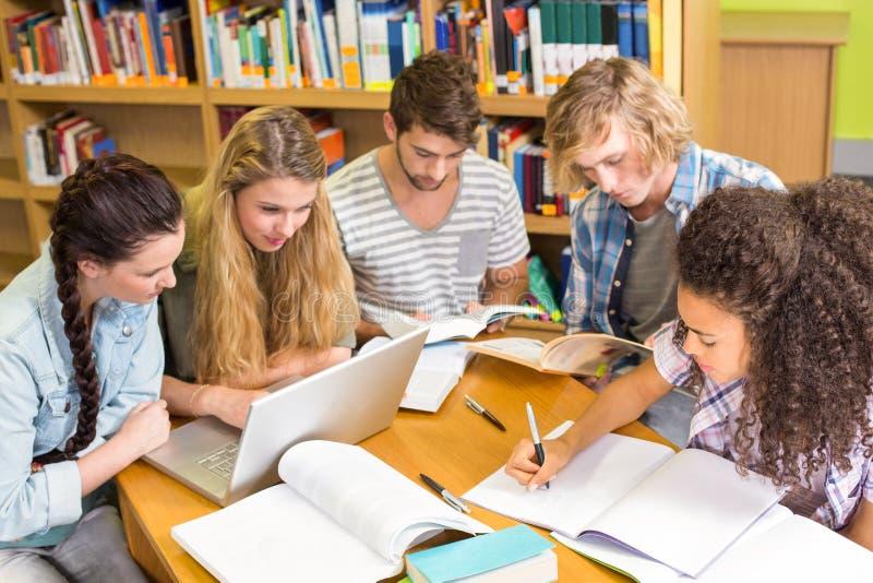 Студенты колледжа делая домашнюю работу в библиотеке стоковое изображение rf