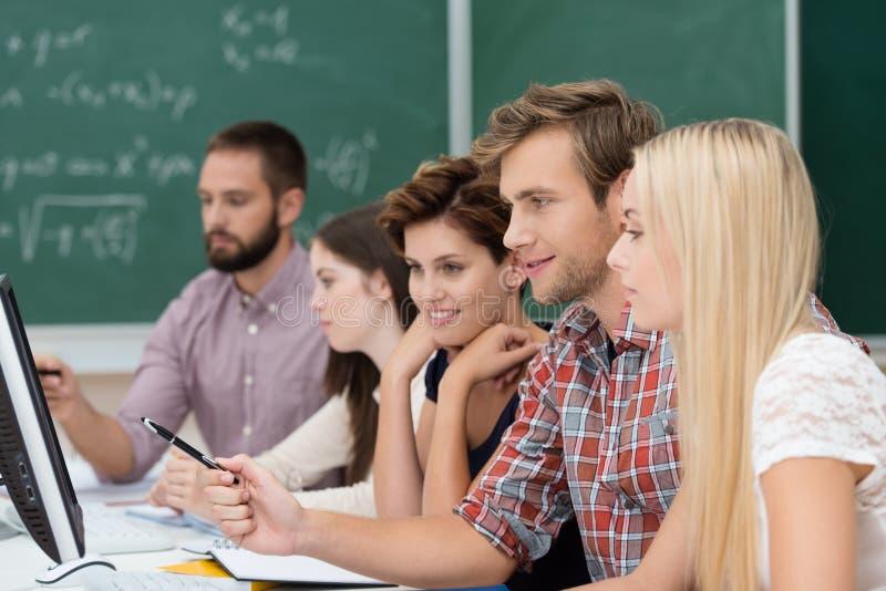 Студенты колледжа изучая используя компьютер стоковые изображения rf