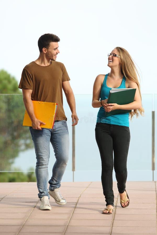 Студенты мальчик и девушка подростка идя к камере стоковые фото