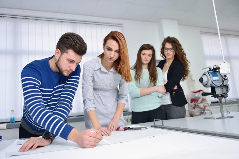 Студенты моды работая в команде на коллеже стоковое изображение