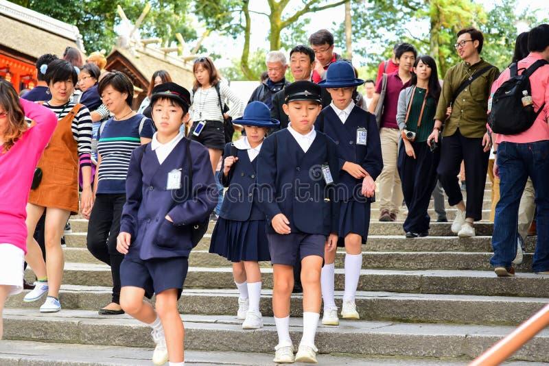 Студенты начальной школы нося школьные формы стоковое изображение