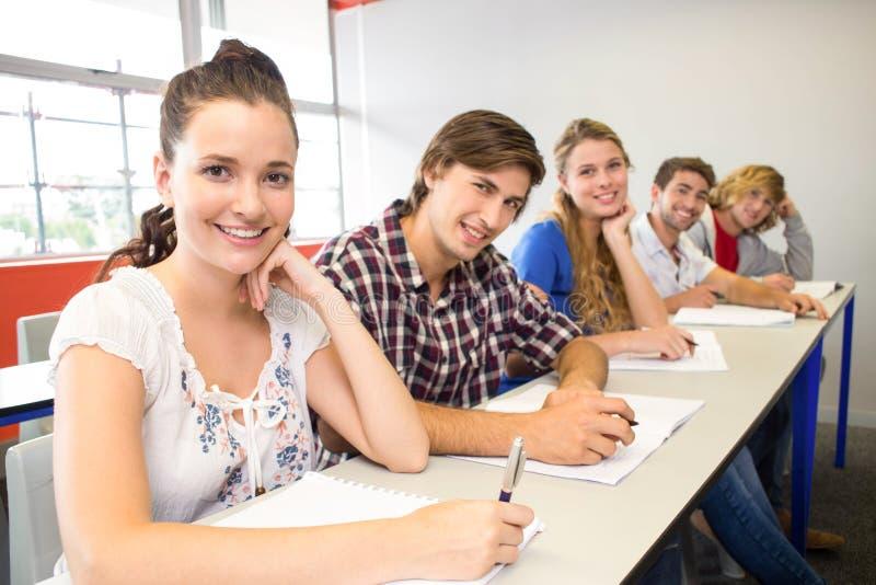 Студенты писать примечания в классе стоковые изображения