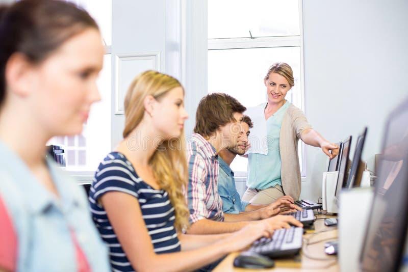 Студенты порции учителя компьютера стоковая фотография rf