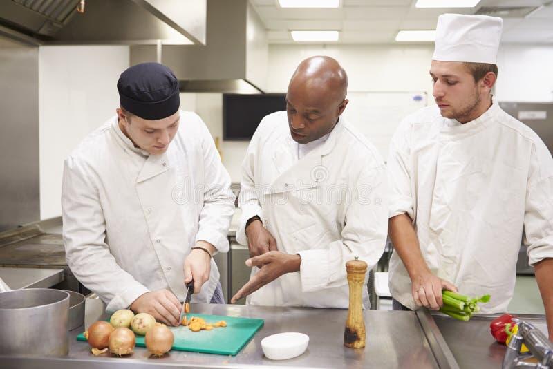 Студенты порции учителя тренируя для работы в ресторанном обслуживание стоковые фото