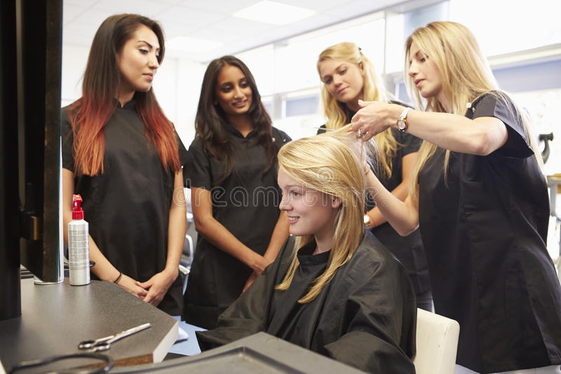 Студенты порции учителя тренируя для того чтобы стать парикмахерами стоковое фото rf
