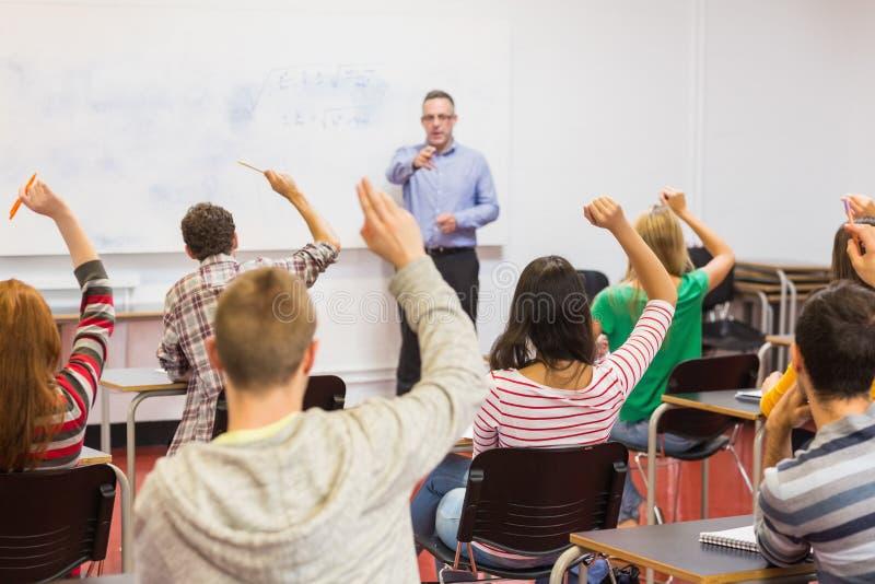 Студенты поднимая руки в классе стоковое изображение rf