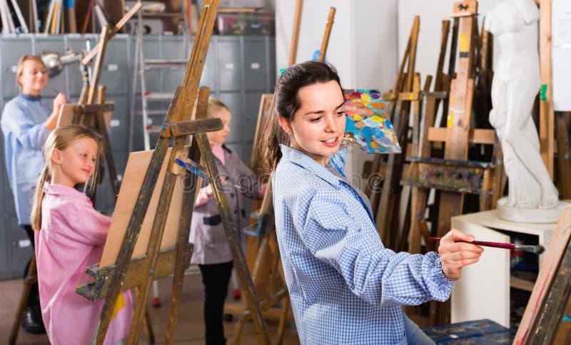 Студенты работая терпеливо во время класса картины на студии искусства стоковая фотография