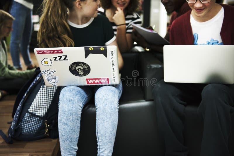 Студенты сидя используя обучение по Интернетуу с компьтер-книжкой стоковые изображения rf