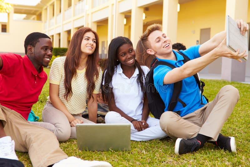 Студенты средней школы принимая Selfie с таблеткой цифров стоковое изображение rf