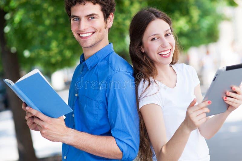 Студенты с книгой и цифровой таблеткой стоковые фотографии rf