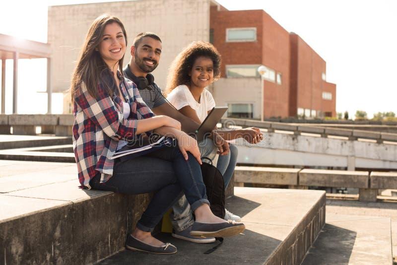 Студенты с компьтер-книжкой в кампусе стоковые фотографии rf