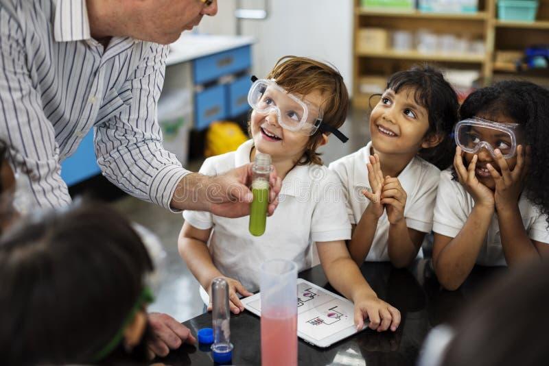 Студенты уча в классе лаборатории эксперименту по науки стоковая фотография rf