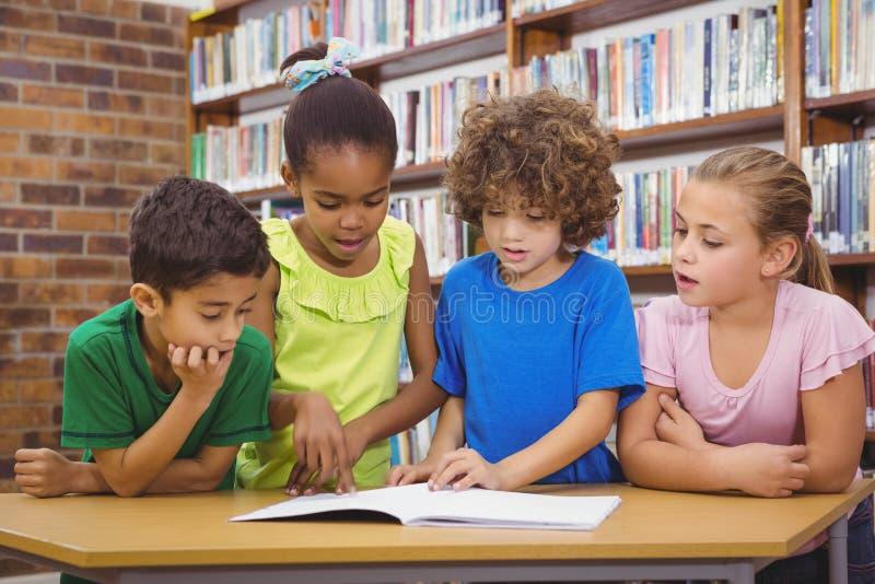 Студенты читая учебник froma стоковые фото