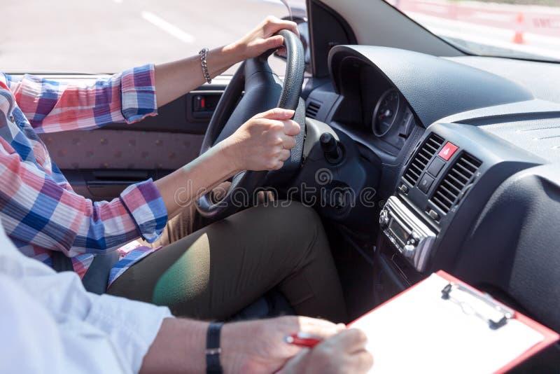 Студент водителя учащийся управляя автомобилем с инструктором стоковое изображение