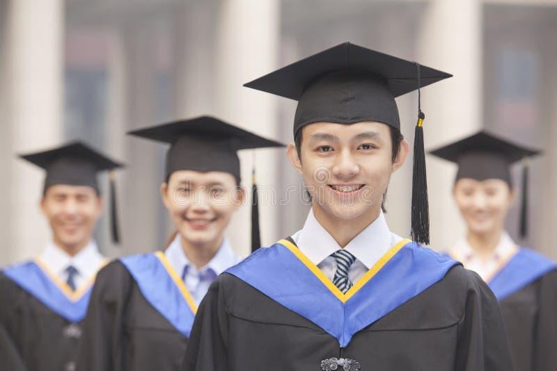 4 студент-выпускника усмехаться университета, смотря камеру стоковое изображение rf