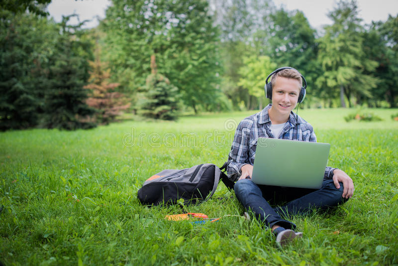Студент в парке кампуса изучая на компьтер-книжке стоковые изображения