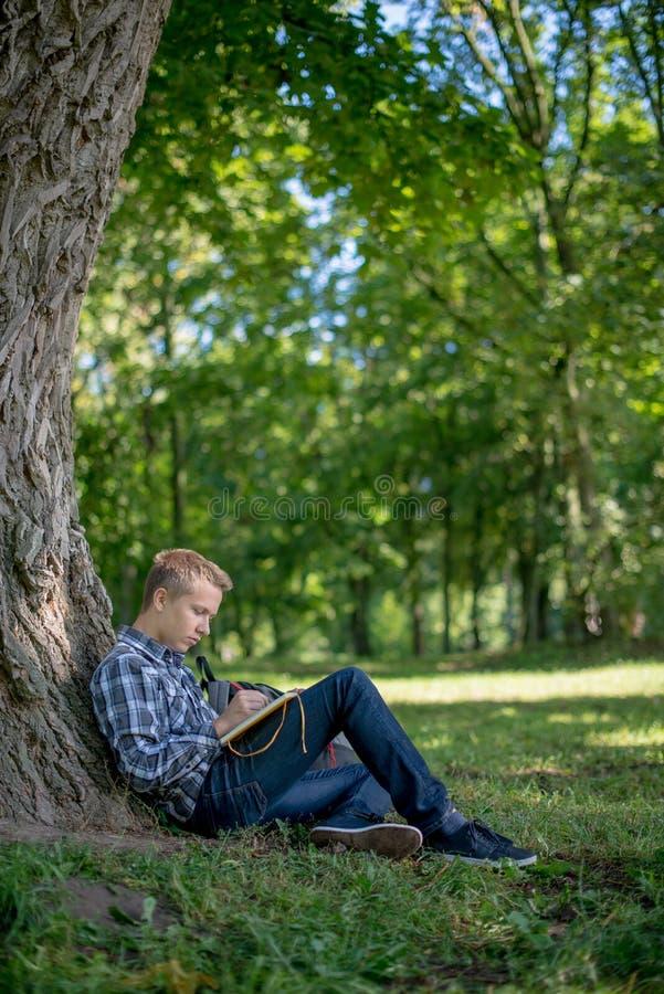 Студент в парке кампуса стоковые фотографии rf