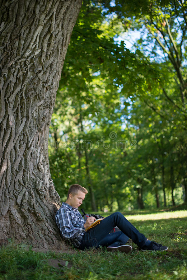 Студент в парке кампуса стоковые изображения rf