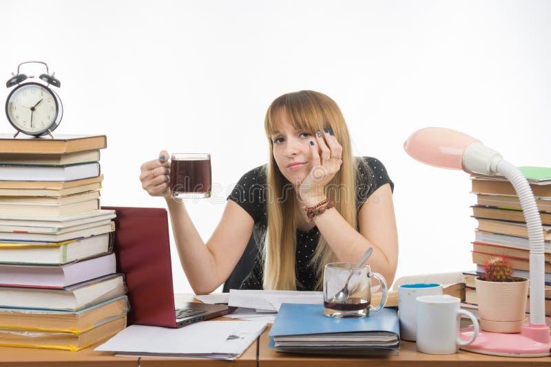 Студент девушки посмотрел уныло в рамку сидя с чашкой кофе в руке стоковое изображение