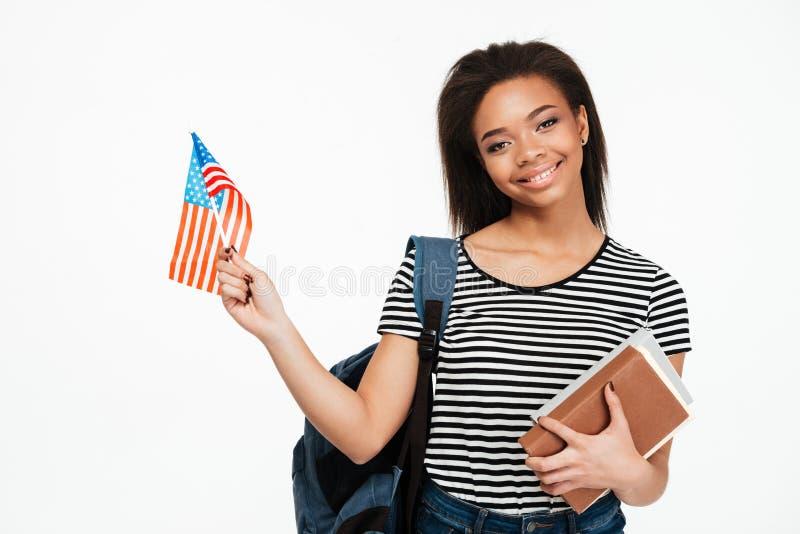 Студент девушки при рюкзак держа книги и США сигнализируют стоковое изображение rf