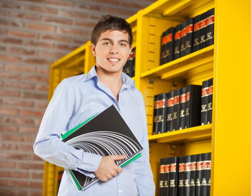 Студент держа книги готовя полку в библиотеке стоковая фотография
