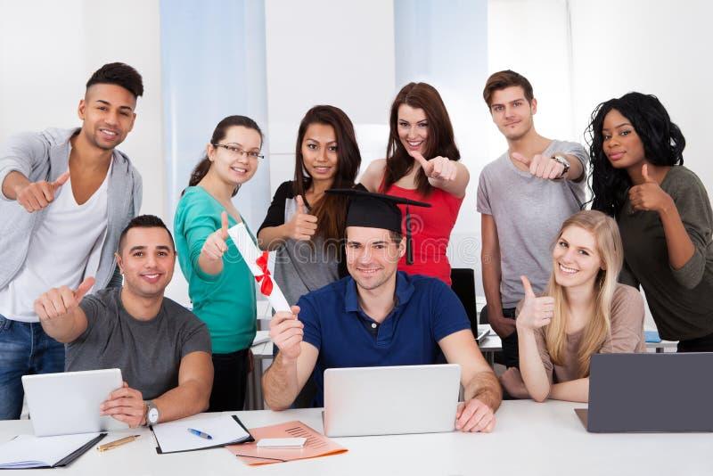 Студент держа степень при одноклассники показывать большие пальцы руки вверх стоковые изображения rf
