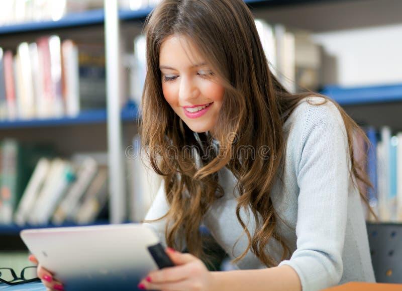 Студент используя таблетку в библиотеке стоковые изображения rf