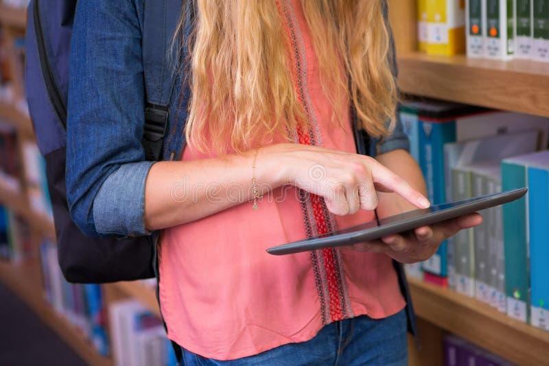 Студент используя таблетку в библиотеке стоковые изображения