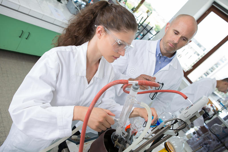 Студент и учитель работая на робототехнической руке совместно стоковое фото rf