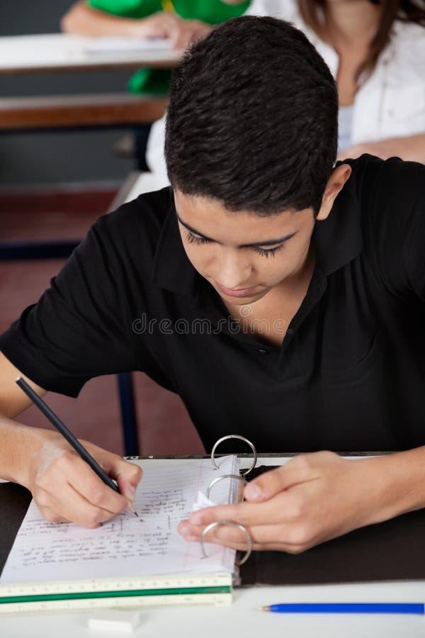 Студент копируя от шпаргалки на столе стоковое изображение rf