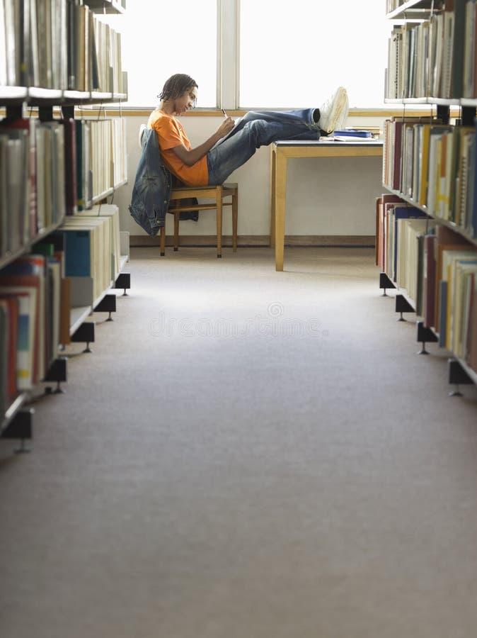 Студент колледжа делая домашнюю работу в библиотеке стоковое фото rf
