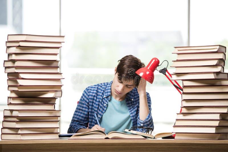 Студент молодого человека подготавливая для экзаменов коллежа стоковые изображения rf